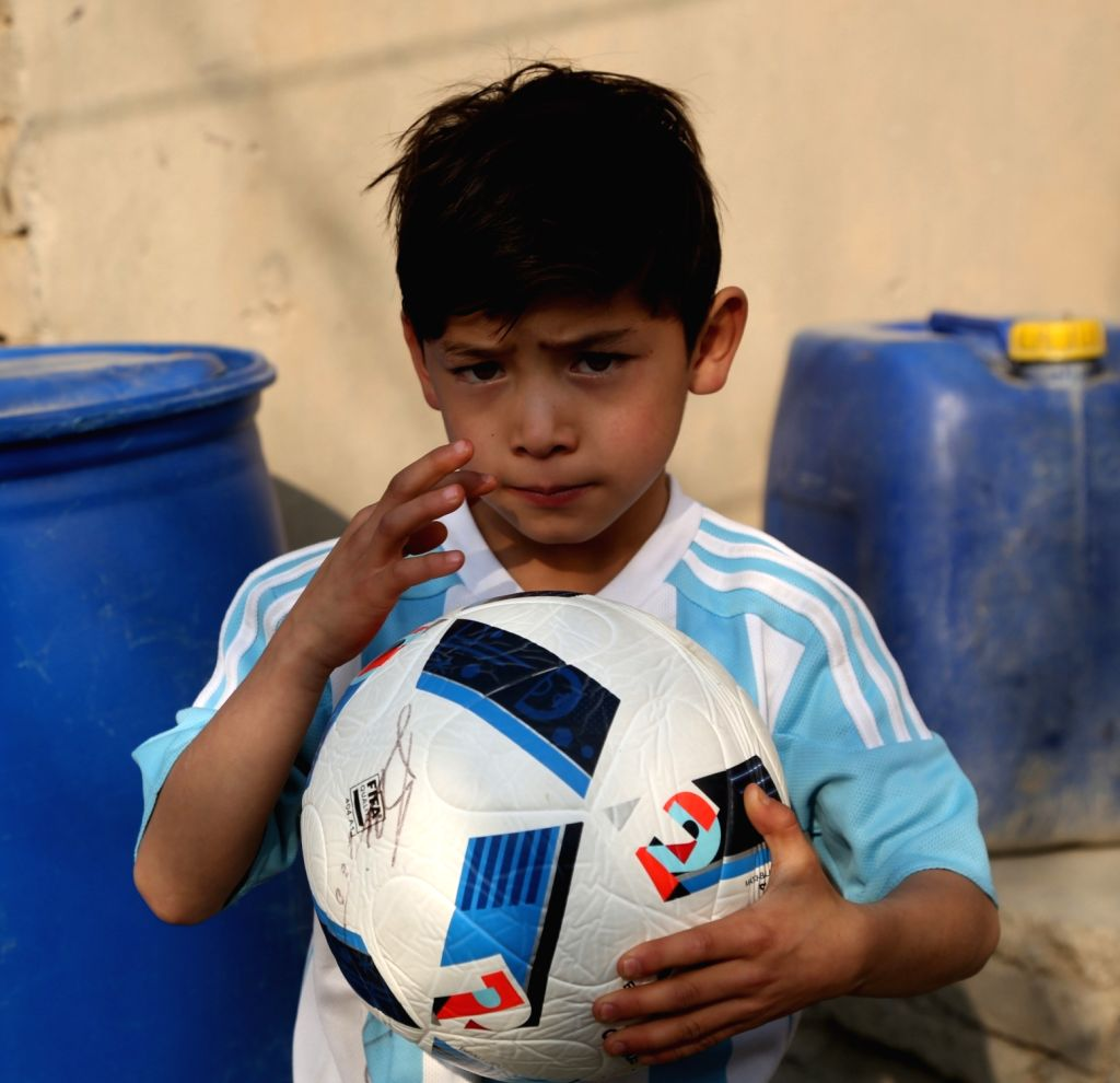 KABUL, Dec. 10, 2018 - Afghanistan little Messi fan Murtaza Ahmadi shows signature on a ball signed by Argentina soccer player Lionel Messi in Kabul, capital of Afghanistan, Dec.8, 2018.