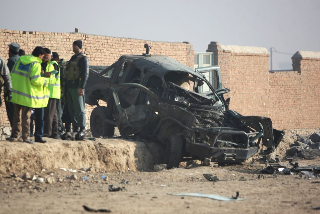 Investigators inspect the site of car bombing in Kabul, Afghanistan, on Dec. 18, 2014. One policeman was killed and three others were wounded after a suicide bomber ..