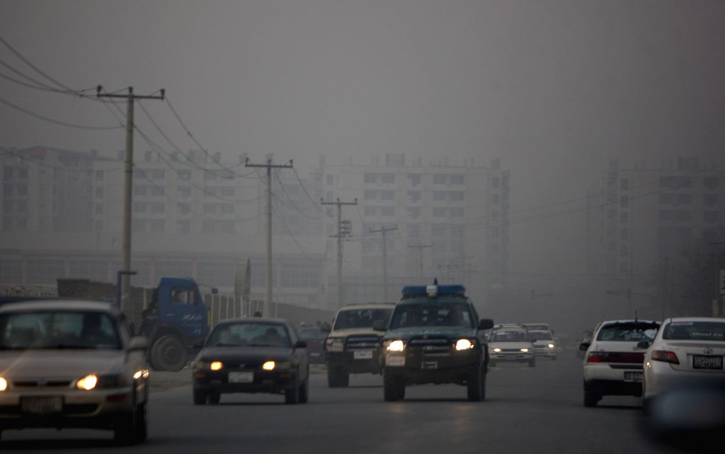 Vehicles drive along a road in heavy fog in Kabul, capital of Afghanistan, on Dec. 17, 2014.