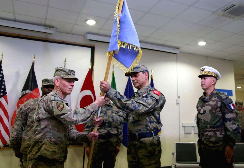 NATO Air Command-Afghanistan Commander U.S. Major General John K. McMullen (L, front) gives ceremonial flag to incoming commander Major General Mehmet Cahit Bakir ...