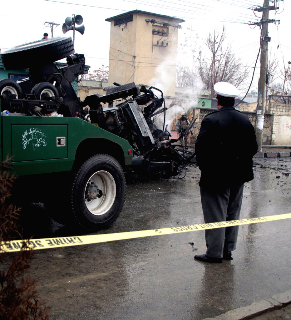 A damaged vehicle is seen in the scene following a blast in Kabul, Afghanistan, Jan. 13, 2015. Two civilians were killed while two others wounded in a bomb attack in .