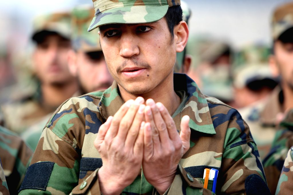 Afghan National Army soldiers pray during their graduation ceremony in Kabul, Afghanistan, Jan. 18, 2015. A total of 200 National Army officers graduated after ...