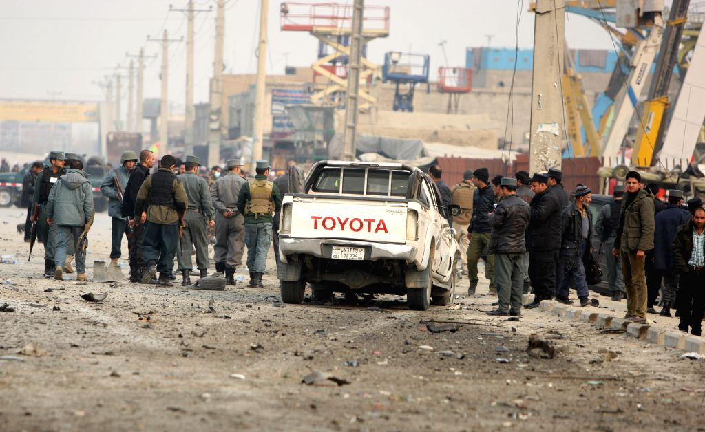 Afghan policemen gather around a destroyed foreign vehicle at the suicide car bombing site following a car bombing in Kabul, Afghanistan, Jan. 5, 2015. A power blast ..