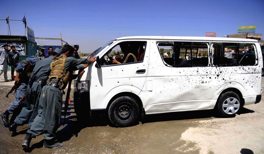 Afghan policemen push a damaged bus at the blast site in Kabul, Afghanistan, July 15, 2014. At least two people were killed while five others were wounded in the bomb
