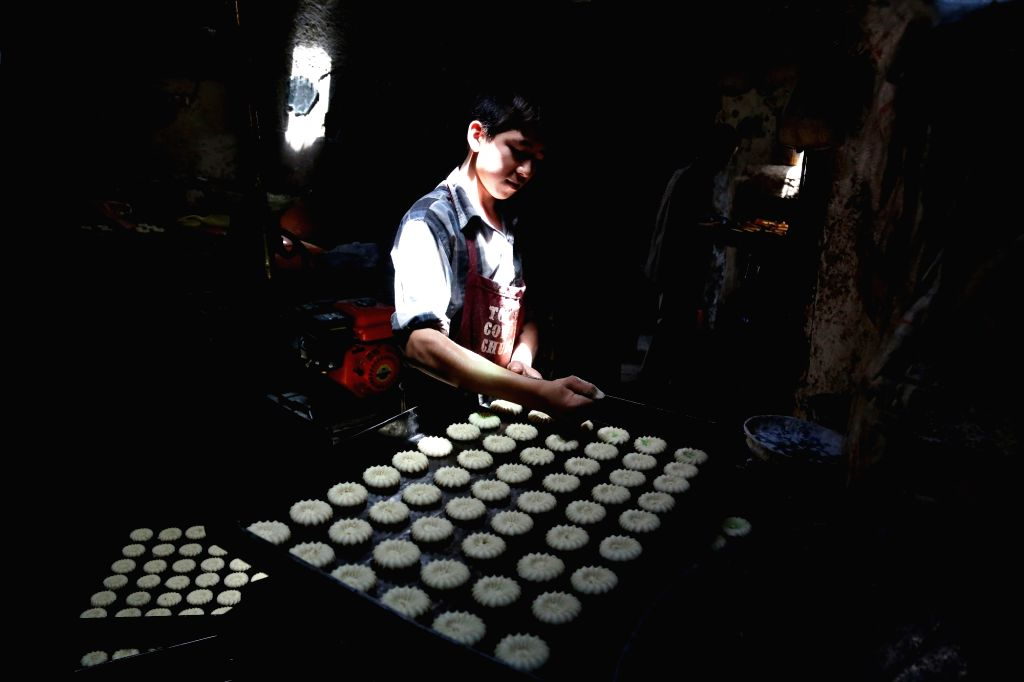 KABUL, June 27, 2016 - An Afghan boy makes cakes for the upcoming Eid al-Fitr festival at a cake factory in Kabul, Afghanistan, June 27, 2016. Muslims are preparing to celebrate the Eid al-Fitr ...