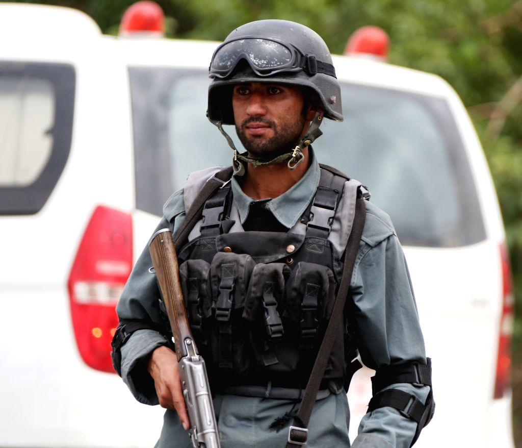 KABUL, June 30, 2016 - An Afghan policeman stands guard at the site of a suicide attack in Kabul, Afghanistan, June 30, 2016. Two suicide explosions hit Afghan police convey of five buses in the ...