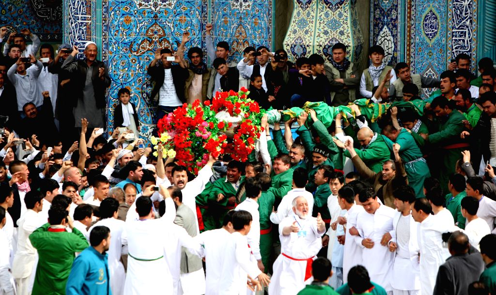 Afghan people raise up a holy mace during a celebration of Nowruz festival in Kabul, Afghanistan, March 21, 2015. Afghans celebrate the Nowruz festival as the first ...