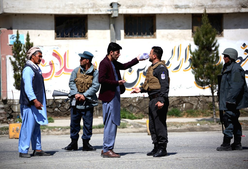 KABUL, March 21, 2018 - Afghan policemen blockade a road near the site of a suicide attack in Kabul, capital of Afghanistan, March 21, 2018. Up to 26 people were killed and 18 others wounded after a ...