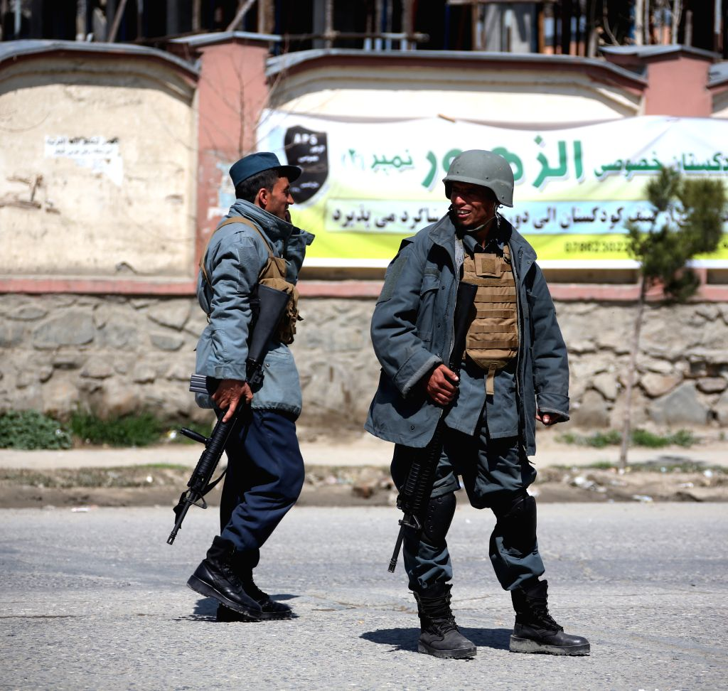 KABUL, March 21, 2018 - Afghan policemen stand near the site of a suicide attack in Kabul, capital of Afghanistan, March 21, 2018. Up to 26 people were killed and 18 others wounded after a suicide ...
