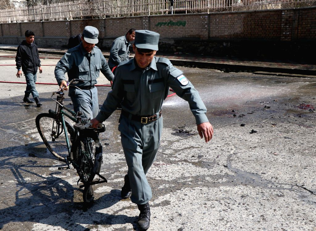 KABUL, March 21, 2018 - Afghan security force members carry a damaged bicycle from the site of a suicide attack in Kabul, capital of Afghanistan, March 21, 2018. Up to 26 people were killed and 18 ...