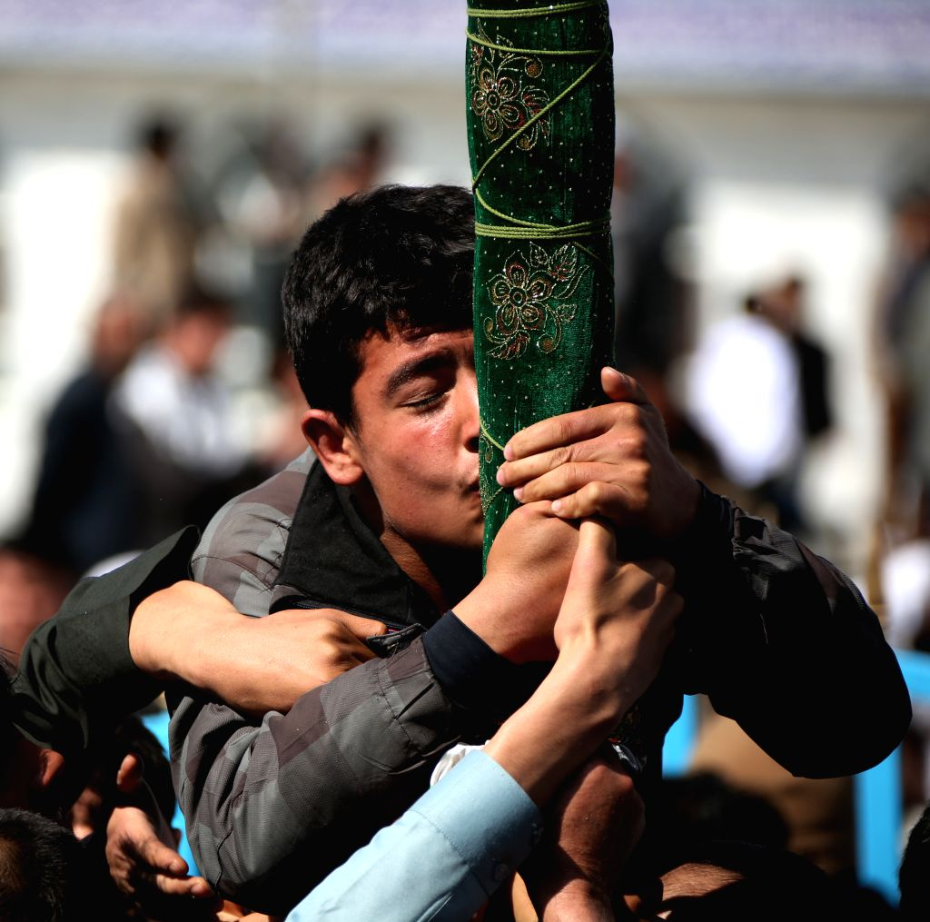 KABUL, March 21, 2018 - An Afghan man kisses a holy stick during the celebration of annual Nawroz Festival in Kabul, capital of Afghanistan, March 21, 2018.