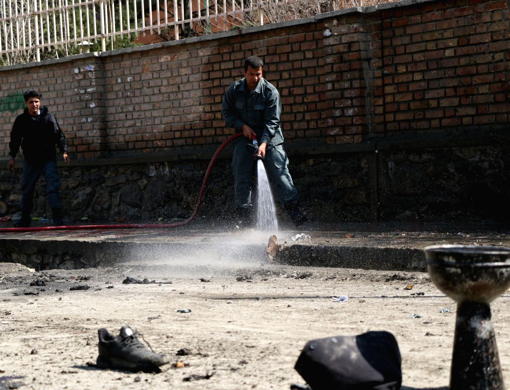 KABUL, March 21, 2018 - An Afghan security force member washes a road near the site of a suicide attack in Kabul, capital of Afghanistan, March 21, 2018. Up to 26 people were killed and 18 others ...