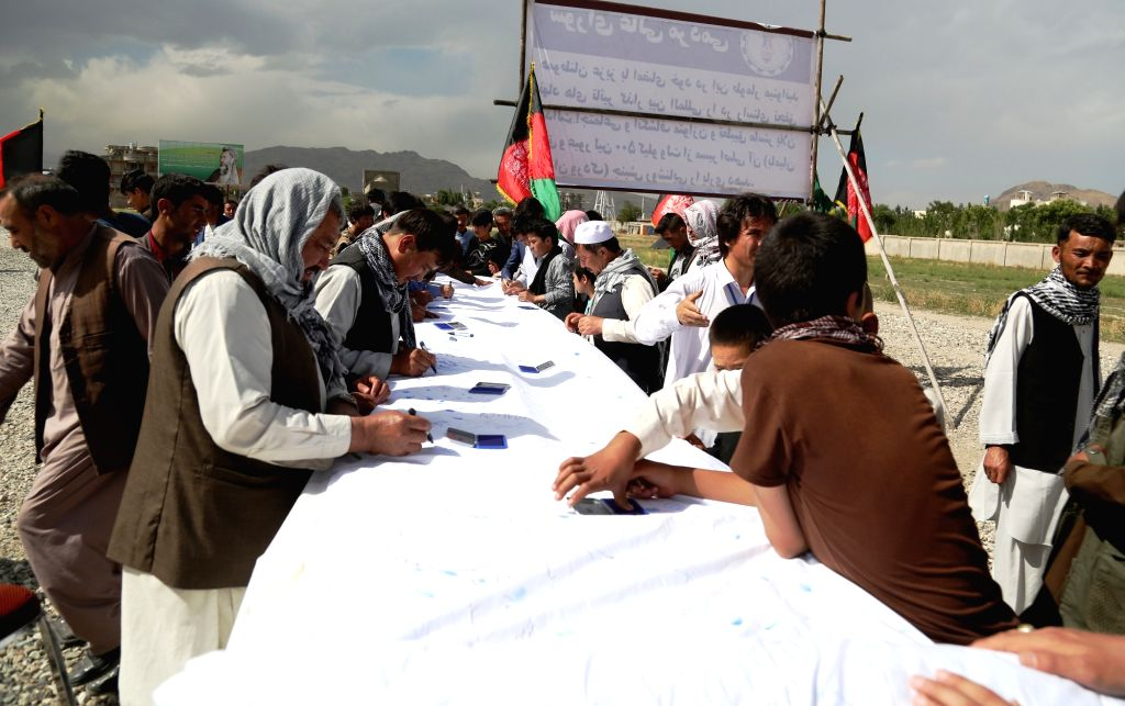 KABUL, May 28, 2016 - Afghan protesters sign on a banner during a protest in Kabul, capital of Afghanistan, May 27, 2016. Thousands of Afghans gathered at a mosque west of Kabul on Friday to protest ...
