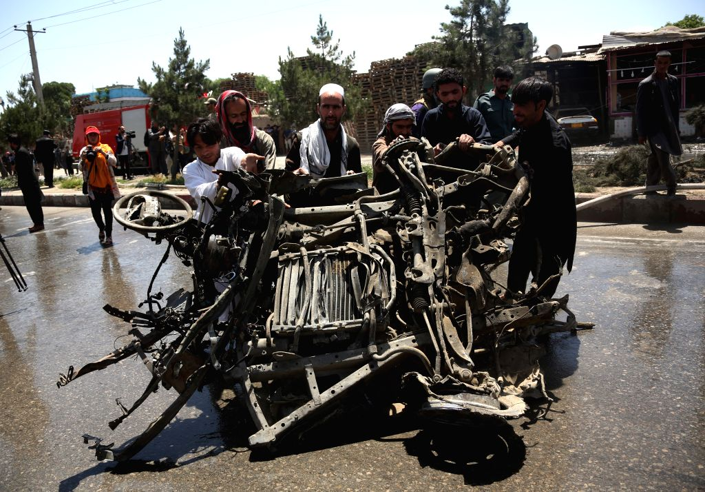 KABUL, May 31, 2019 - Local people move a damaged car from the site of an attack in Kabul, capital of Afghanistan, May 31, 2019. At least four people were killed and three others injured, all of whom ...