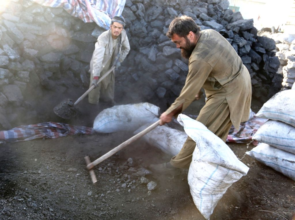Afghan labors work at a coal market in Kabul, capital of Afghanistan, Nov. 17, 2015. Afghans are preparing heating materials for the upcoming winter in the mountainous ...