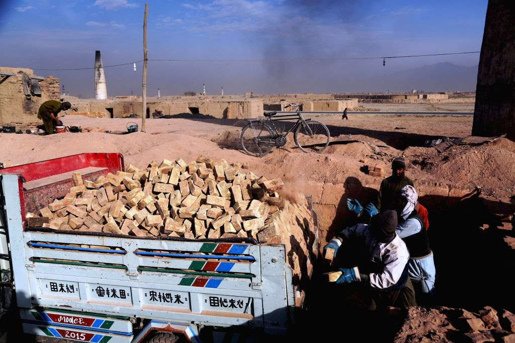 KABUL, Nov. 20, 2016 - Afghan men load bricks onto a truck at a brick factory in Kabul, capital of Afghanistan, Nov. 20, 2016. Some 16 million people in the country are eligible to work and out of ...