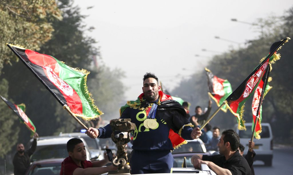 KABUL, Oct. 11 Afghan body building champion Ahmad Yasin Salik Qaderi (C) who claimed the title of Mr. Universe 2017 in Mongolia's Ulaanbaatar, stands on a vehicle during a celebrating ...