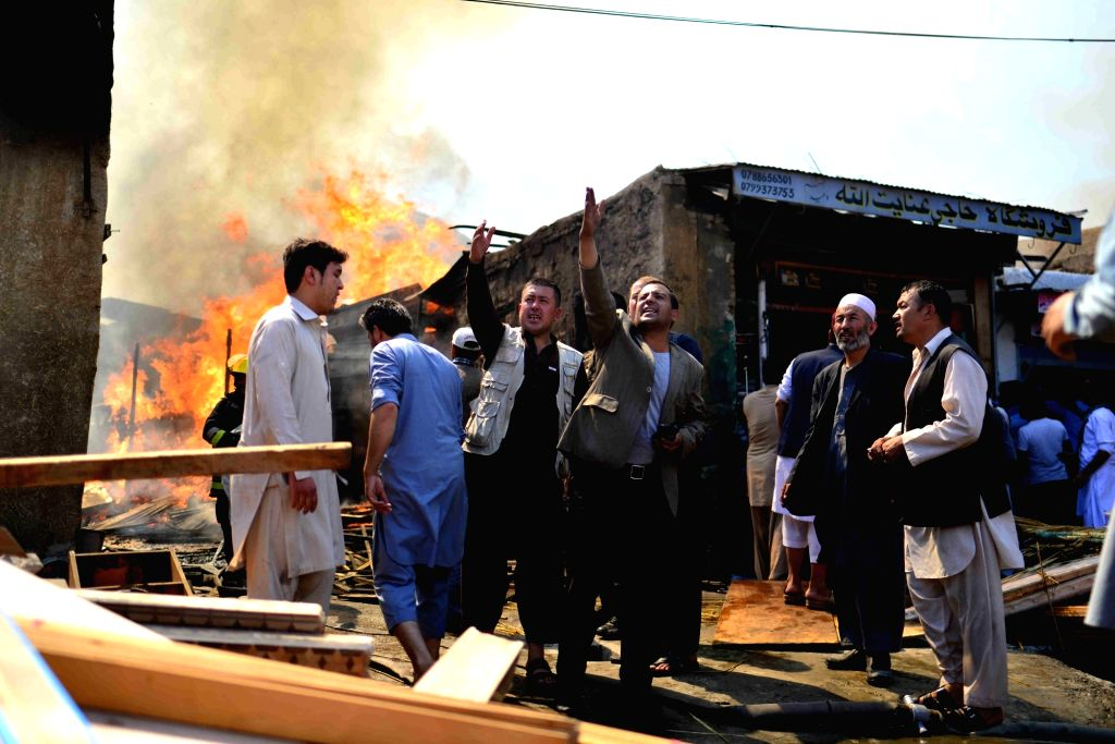 KABUL, Sept. 18, 2016 - Merchants appeal to firefighters for extinguishing a fire at a market in Kabul, capital of Afghanistan, on Sept. 18, 2016. A fire broke out in a construction wood market in ...