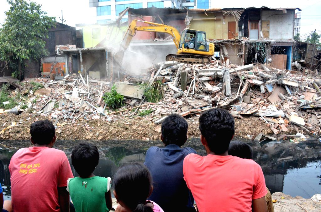 Kamrup Metropolitan district administration carries on a demolition drive against illegal sturctures along the Bharalu River near Sarab Bhatti in Guwahati on July 2, 2014.