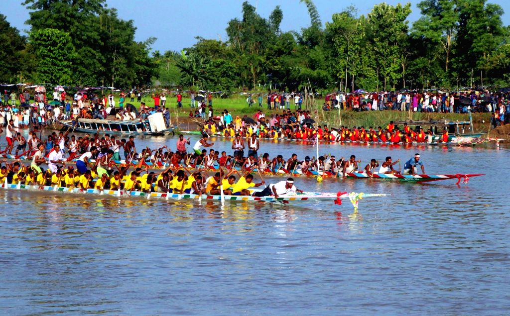 Kamrup: People participates in a traditional boat race competition on Mora Kalahi River at Sampupara in Assam's Kamrup district on Aug 18, 2019. (Photo: IANS)