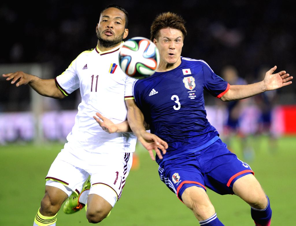 Juan Falcon (L) of Venezuela and Gotoku Sakai of Japan vie for the ball during their Kirin Challenge Cup match in Yokohama, south of Tokyo, Japan, Sept. 9, 2014. ..