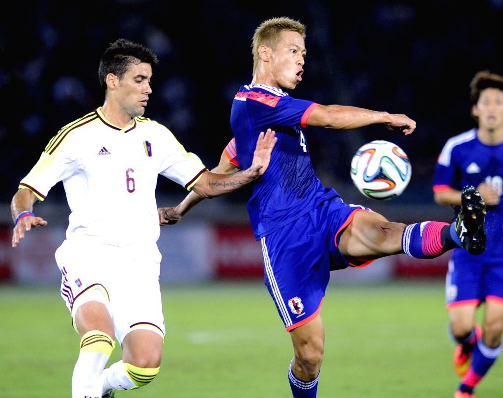 Keisuke Honda (R, front) of Japan and Gabriel Cichero of Venezuela vie for the ball during their Kirin Challenge Cup match in Yokohama, south of Tokyo, Japan, ...