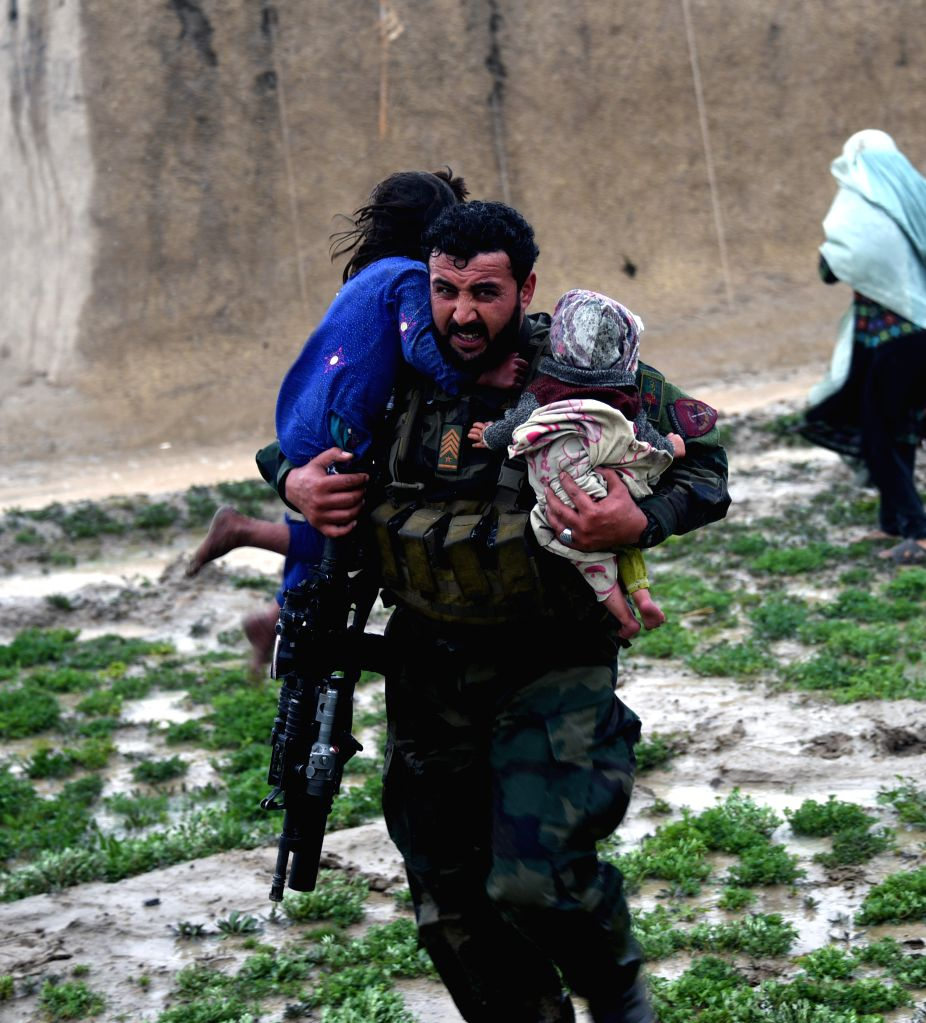 KANDAHAR, March 3, 2019 (Xinhua) -- An Afghan security force member rescues children during an evacuation operation after a flood in Kandahar province, Afghanistan, March 2, 2019 . At least 20 people were killed and many others went missing after fla