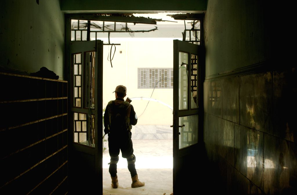 An Afghan policeman stands guard at the site of blast in Kandahar province, south Afghanistan, March 31, 2015. One person was injured after a blast rocked ...