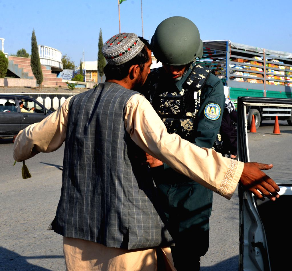 KANDAHAR, Oct. 4, 2017 - An Afghan policeman inspects a man during a military operation in Kandahar province, southern Afghanistan, Oct. 4, 2017. Up to 81 militants have been killed and 19 others ...