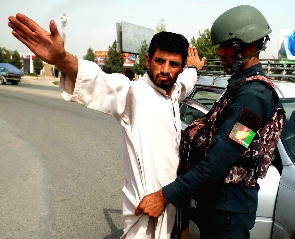 KANDAHAR, Sept. 16, 2018 - An Afghan security force member checks a man at a security checkpoint in Kandahar city, capital of Kandahar province, Afghanistan, Sept. 16, 2018. Unknown armed militants ...