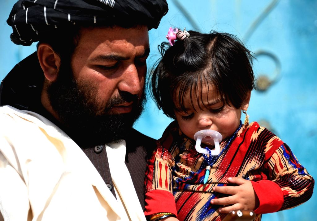 KANDAHAR, Sept. 27, 2018 (Xinhua) -- A man holds his daughter, who has been infected by polio, in Kandahar city, capital of Kandahar province, southern Afghanistan, Sept. 27, 2018. A fresh infectious poliomyelitis case has been detected in Afghanista