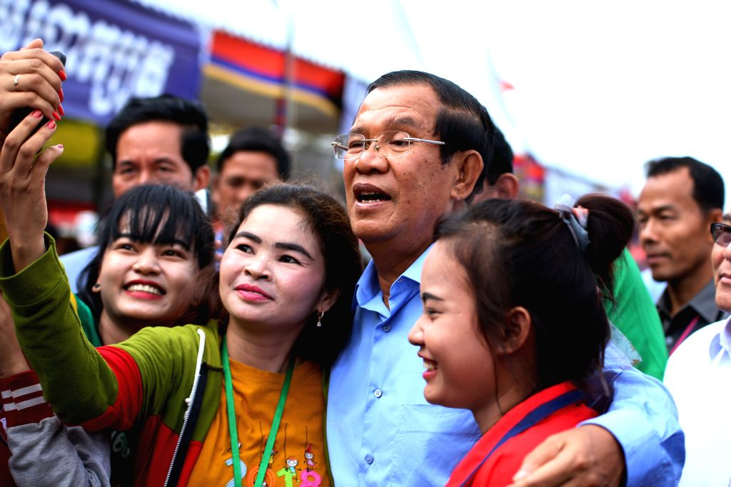 KANDAL, July 5, 2018 - Cambodian Prime Minister Samdech Techo Hun Sen (C) poses for a selfie with garment factory workers in Kandal province, Cambodia, on July 5, 2018. Hun Sen on Thursday called for ... - Samdech Techo Hun Sen