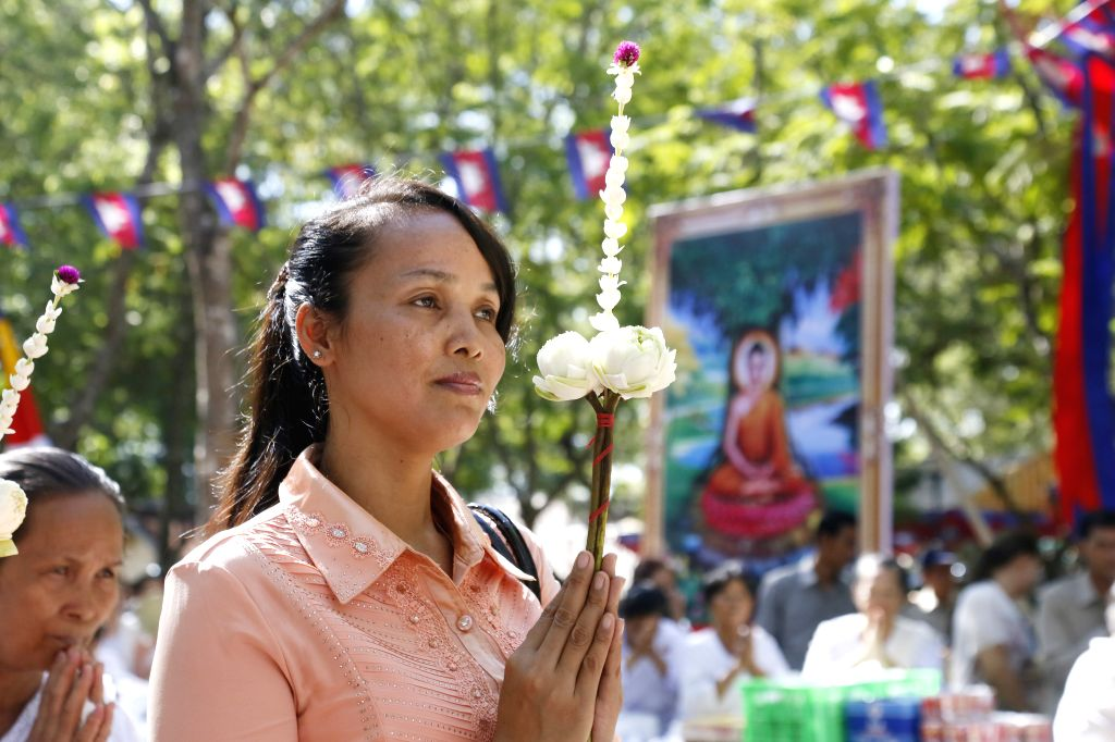 A woman prays on the Visak Bochea Day, or Lord Buddha's Day, in Kandal province, Cambodia, May 13, 2014. Hundreds of Buddhist monks and laypeople celebrated the Visak