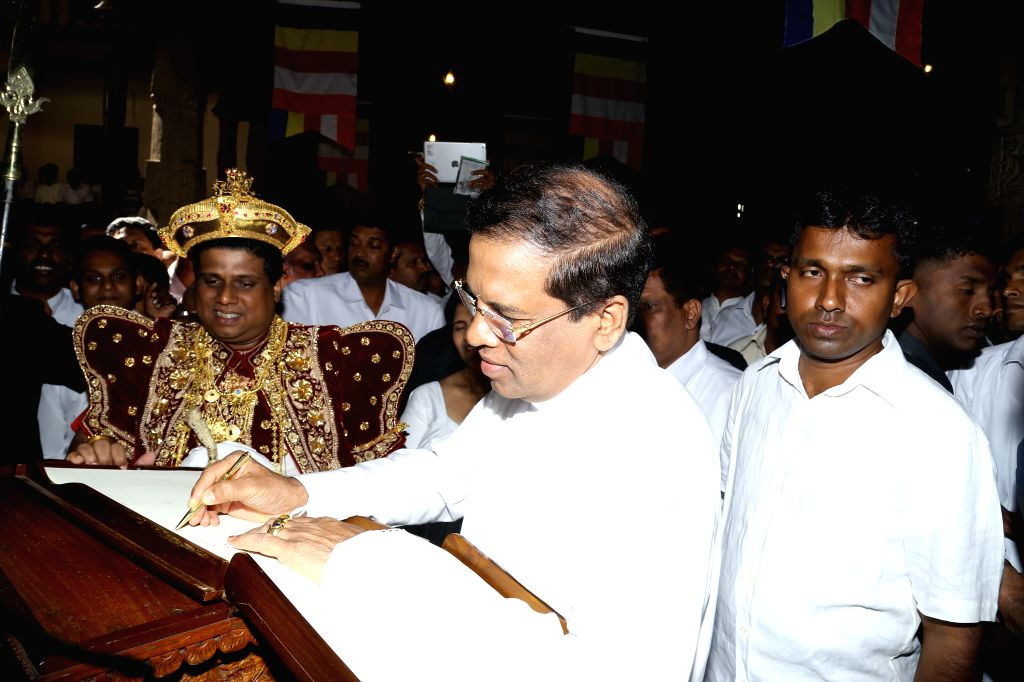New President Maithripala Sirisena of Sri Lanka signs on a book of visitors at the Temple of Tooth in Kandy, Sri Lanka, on January 11, 2015.  In Sri Lanka where 70 ...