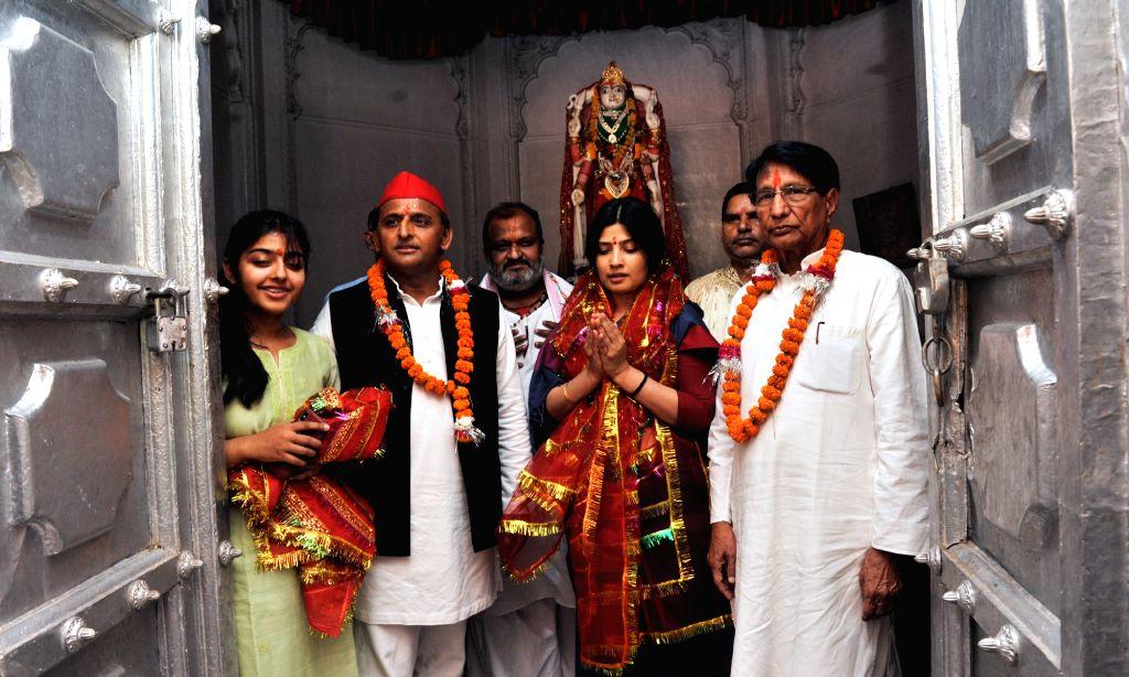 Kannauj: Samajwadi Party President Akhilesh Yadav, his wife and the party's Lok Sabha candidate from Kannauj, Dimple Yadav and Rashtriya Lok Dal (RLD) chief Ajit Singh during their visit to the Ma Annapurna Temple, in Uttar Pradesh's Kannauj, on Apri - Akhilesh Yadav and Ajit Singh