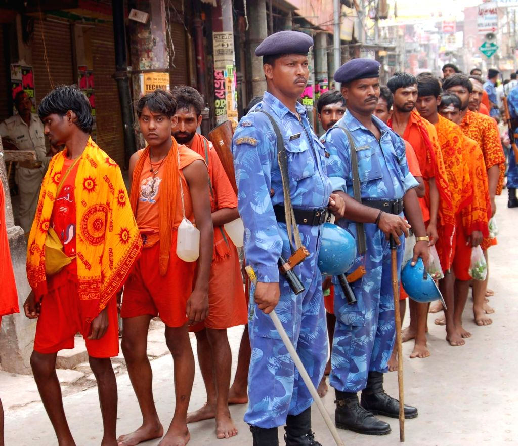 Kanwariyas - devotees of lord Shiva - queue-up outside Kashi Vishwanath Temple amid tight security on the second Monday of the holy month of Sawan in Varanasi on Aug 1, 2016.