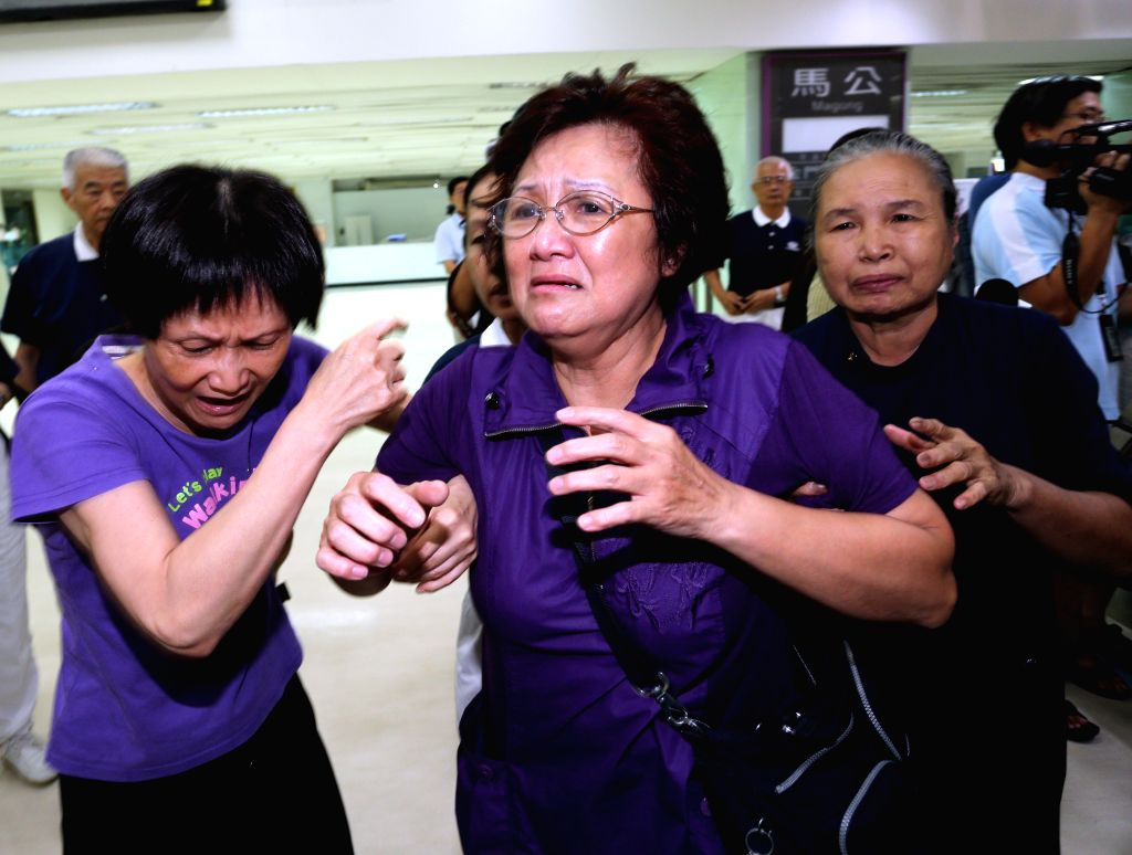 Relatives of passengers onboard TransAsia Airways' flight GE222, which ended up in a failed emergency landing, are seen at Kaohsiung International Airport in ...