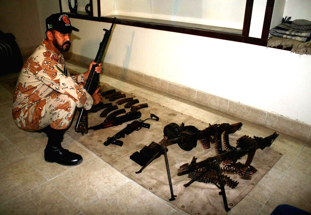 A Pakistani ranger displays seized weapons in southern Pakistani port city of Karachi on April 14, 2014. Pakistani police arrested 100 suspects and seized weapons .