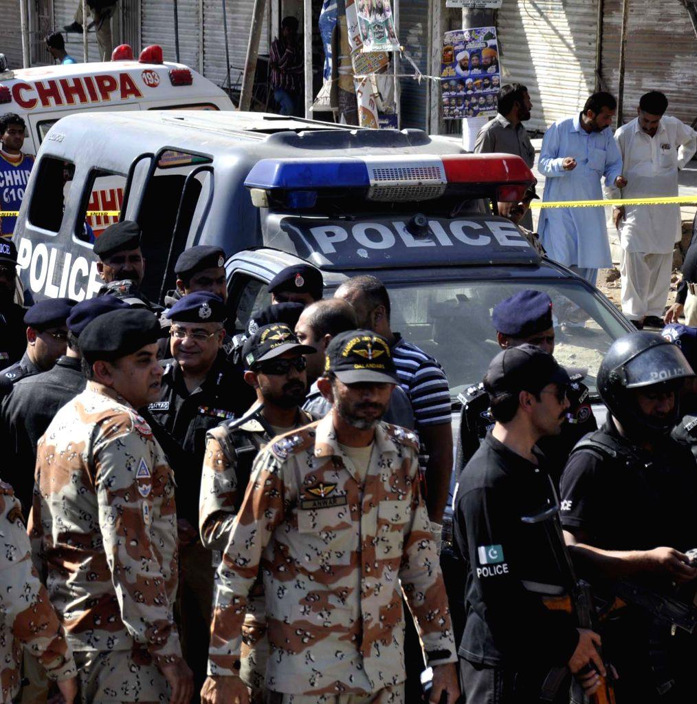 KARACHI, April 20, 2016 - Pakistani paramilitary soldiers gather around a police van at the attack site in southern Pakistani port city of Karachi, April 20, 2016. At least seven policemen, deployed ...