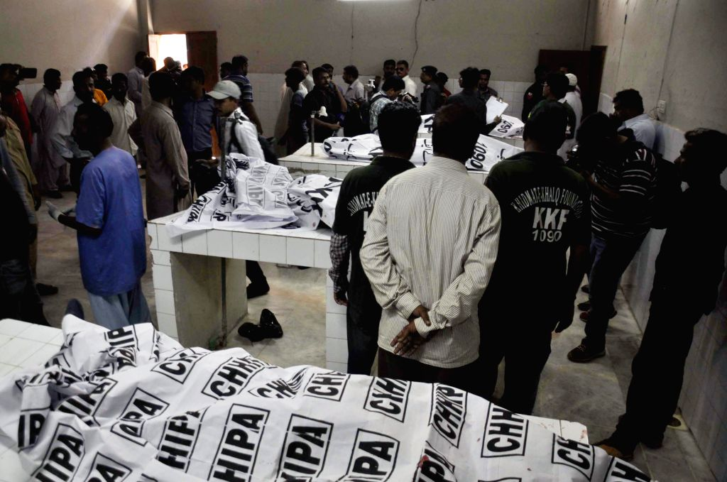 KARACHI, April 20, 2016 - Pakistani people and hospital staff gather around bodies of policemen at a hospital in southern Pakistani port city of Karachi, April 20, 2016. At least seven policemen, ...