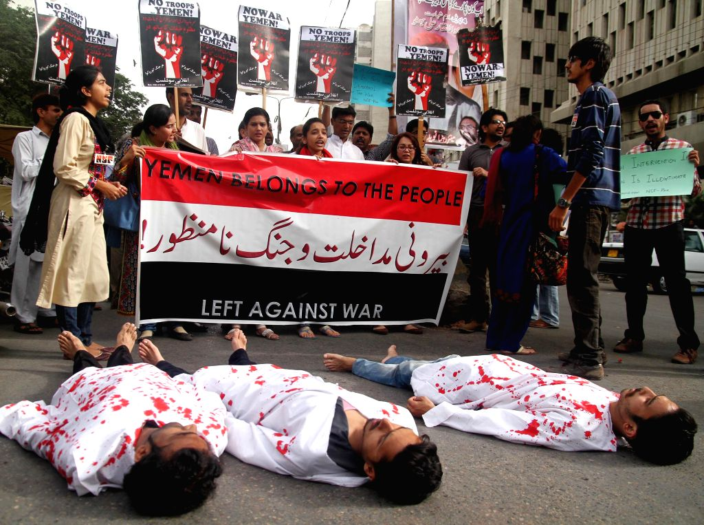 Pakistani anti-war activists wrap themselves with shrouds during a protest to condemn Saudi Arabia-led airstrikes on Yemen, in southern Pakistani port city of ...