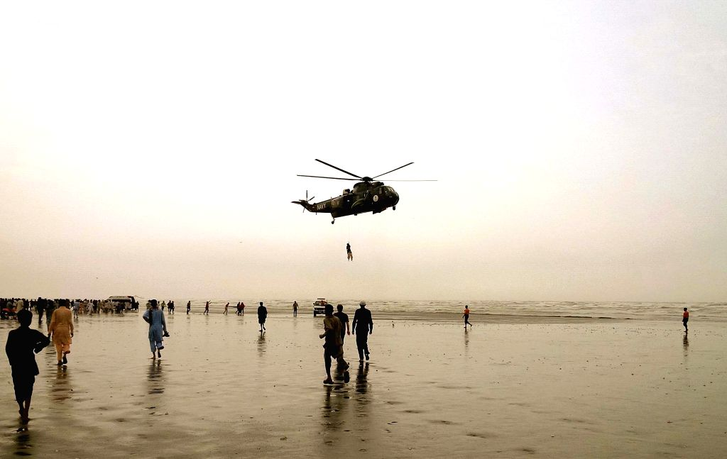 A Pakistan Navy Sea King helicopter is seen with a frogman attached to a winch line from the aircraft, transports a recovered body of a drowning victim over Clifton .