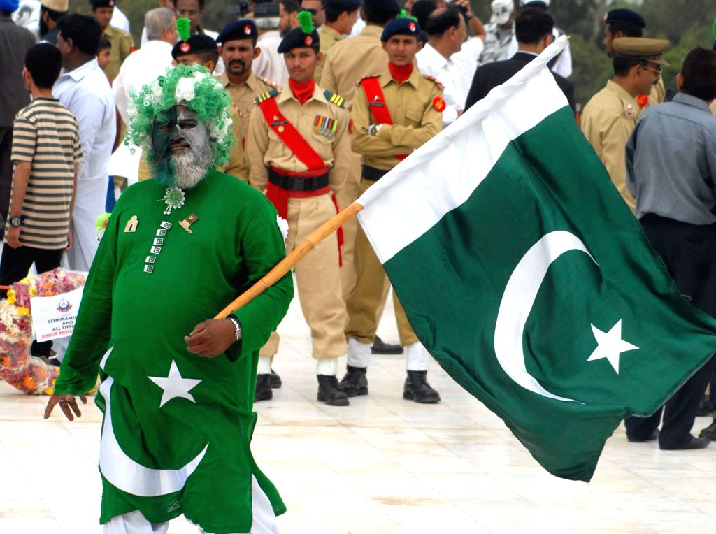 KARACHI, Aug. 14, 2016 - A Pakistani man holds a national flag during a ceremony to mark the Independence Day at the mausoleum of Pakistani founding father Muhammad Ali Jinnah, in southern Pakistani ...