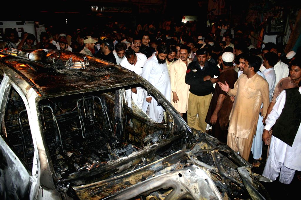People gather around the wreckage of a destroyed vehicle at the blast site in southern Pakistani port city of Karachi on Dec. 20, 2013. At least three people ..
