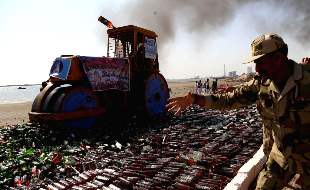 KARACHI, Feb. 12, 2019 - A steamroller rolls over bottles of liquor during a ceremony in Pakistan's southern port city of Karachi on Feb. 11, 2019. Pakistan Coast Guards on Monday destroyed tons of ...