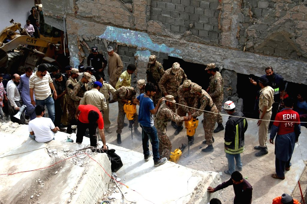 KARACHI, Feb. 25, 2019 - People search for victims in the rubble of a collapsed three-storey residential building in southern Pakistani port city of Karachi on Feb. 25, 2019. A three-storey ...