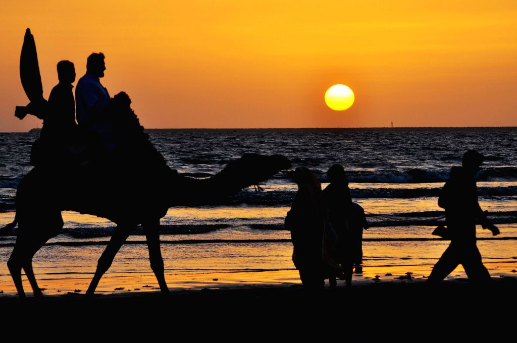Tourists ride on a camel at a beach during sunset in southern Pakistani port city of Karachi, Feb. 27, 2015.