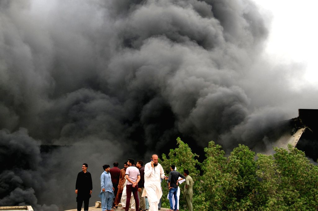 KARACHI, July 5, 2018 - People gather as smoke rages from a factory in southern Pakistani port city of Karachi on July 5, 2018. At least six firefighters were injured while battling a huge ablaze ...