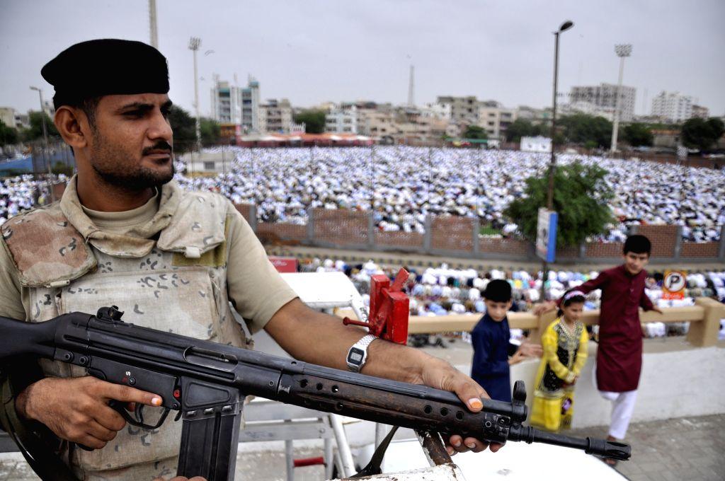 KARACHI, July 6, 2016 - A Pakistani soldier stands guard as muslims offer Eid al-Fitr prayers in southern Pakistani port city Karachi on July 6, 2016.