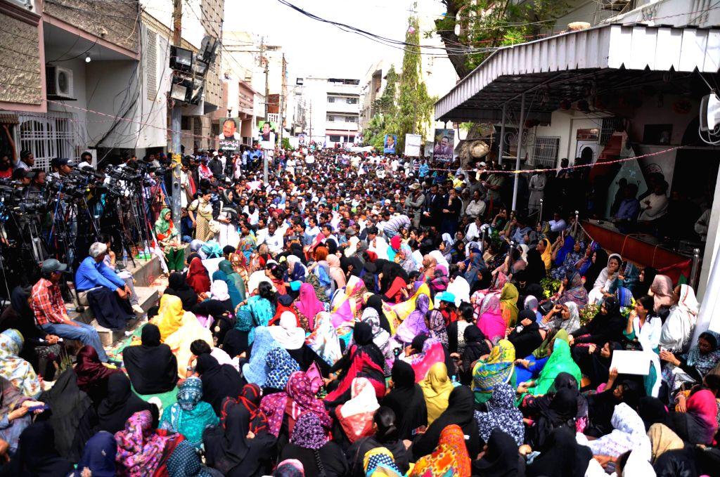 Pakistani supporters of Muttahida Qaumi Movement (MQM) gather outside the MQM headquarters following a raid by paramilitary rangers in southern Pakistani port city ...